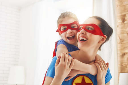 Foto de Mother and her child playing together. Girl and mom in Superhero costume. Mum and kid having fun, smiling and hugging. Family holiday and togetherness. - Imagen libre de derechos