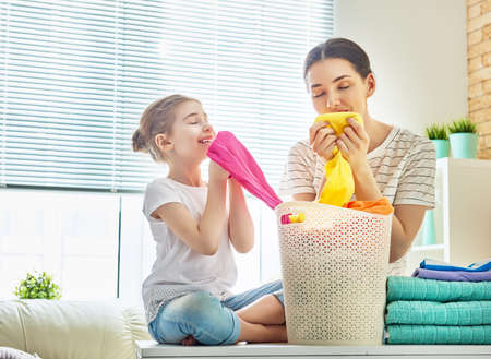Foto de Beautiful young woman and child girl little helper are smelling clean clothes and smiling while doing laundry at home. - Imagen libre de derechos