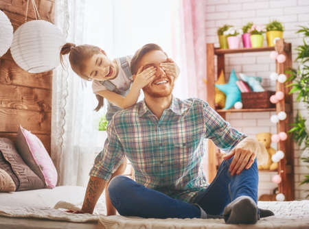 Foto de Happy father's day! Dad and his daughter child girl are playing, smiling and hugging. Family holiday and togetherness. - Imagen libre de derechos