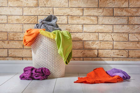 Foto de Basket with colored linen standing on the floor in the laundry room. - Imagen libre de derechos
