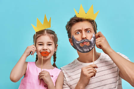 Foto de Funny family on a background of bright blue wall. Father and her daughter girl with a paper accessories. Dad and child are holding paper crown on stick. - Imagen libre de derechos