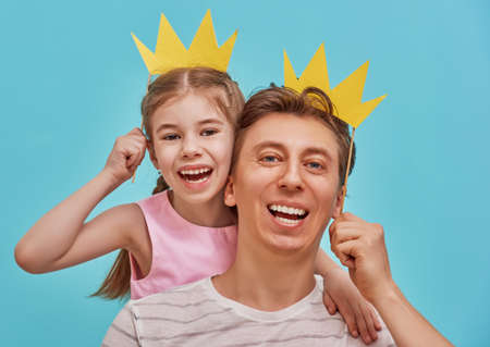 Photo for Funny family on a background of bright blue wall. Father and his daughter girl with a paper accessories. Dad and child are holding paper crown on stick. - Royalty Free Image