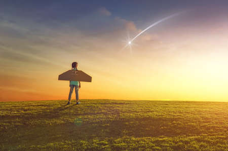Foto de Little girl plays astronaut. Child on the background of sunset sky. Kid is looking at falling star and dreaming of becoming a spaceman. - Imagen libre de derechos