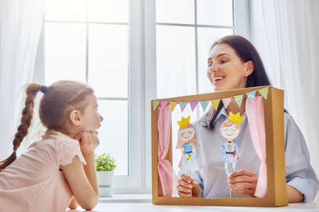 Photo pour Happy loving family. Mother and her daughter in kids room. Funny mom and lovely child having fun and playing performance in the puppet theater indoors. Prince and princess. - image libre de droit