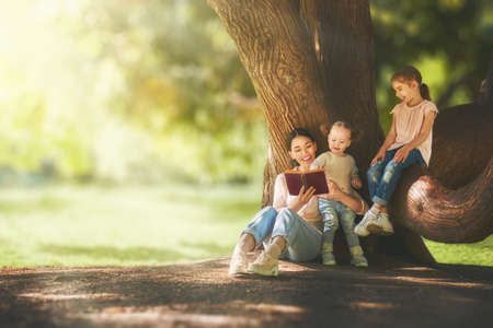 Foto de Mother and daughters sitting under the tree on summer lawn. Happy family playing outdoors. Pretty young mom reading a book to her children in the park outside. - Imagen libre de derechos