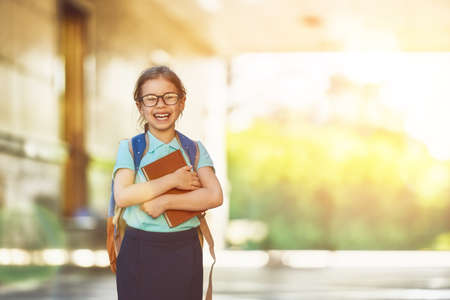 Photo for Pupil of primary school with book in hand. Girl with backpack near building outdoors. Beginning of lessons. First day of fall. - Royalty Free Image
