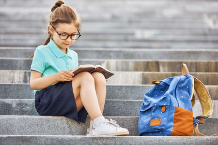 Foto de Pupil of primary school with book in hand. Girl with backpack near building outdoors. Beginning of lessons. First day of fall. - Imagen libre de derechos