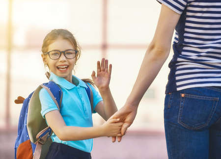 Photo pour Parent and pupil of primary school go hand in hand. Woman and girl with backpack behind the back. Beginning of lessons. First day of fall. - image libre de droit