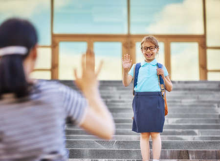 Foto de Parent and pupil of primary school go hand in hand. Woman and girl with backpack behind the back. Beginning of lessons. First day of fall. - Imagen libre de derechos