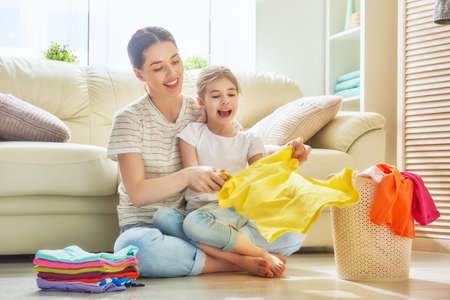 Foto de Beautiful young woman and child girl little helper are having fun and smiling while doing laundry at home. - Imagen libre de derechos