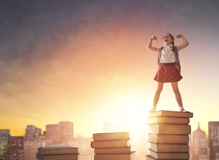 Photo pour Back to school! Happy cute industrious child standing on books on background of sunset urban landscape. Concept of education and reading. The development of the imagination. - image libre de droit