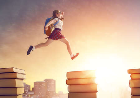 Photo pour Back to school! Happy cute industrious child running and jumping on books on background of sunset urban landscape. Concept of education and reading. The development of the imagination. - image libre de droit