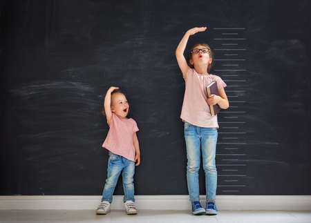Photo pour Two children sisters play together. Kid measures the growth on the background of blackboard. Concept of education. - image libre de droit
