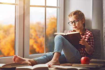 Foto de Cute child girl sitting by the window and reading a book in room at home. Beautiful autumn nature. - Imagen libre de derechos