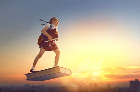 Foto de Back to school! Happy cute industrious child flying on the book on background of sunset urban landscape. Concept of education and reading. The development of the imagination. - Imagen libre de derechos