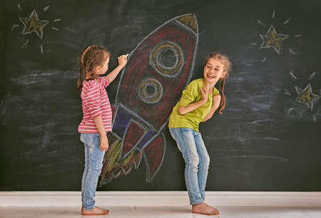 Foto de Back to school! Two happy cute industrious children are drawing stars and rocket on blackboard. Kids are learning in class. - Imagen libre de derechos