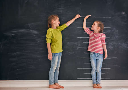 Foto de Two children sisters play together. Kid measures the growth on the background of blackboard. Concept of education. - Imagen libre de derechos