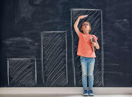 Foto de Cute child is playing. Kid measures the growth on the background of blackboard. Concept of education. - Imagen libre de derechos