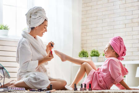 Photo for Happy loving family. Mother and daughter are doing manicures, pedicure, make up and having fun. Mom and child girl are in bathrobes and with towels on their heads. - Royalty Free Image