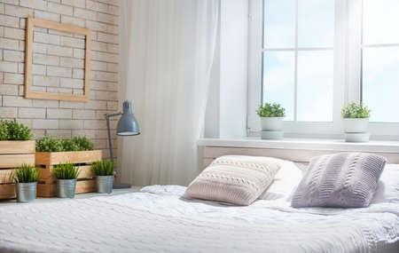 Foto de Bedroom in bright colors. Big comfortable double bed in elegant classic room. - Imagen libre de derechos