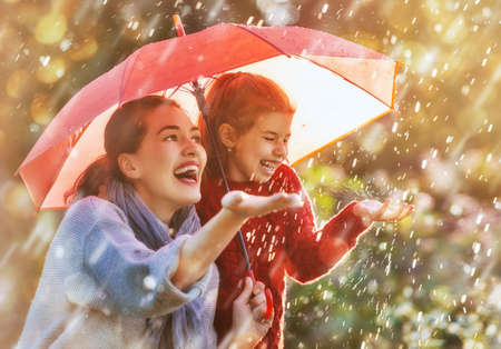 Photo pour Happy funny family with red umbrella under the autumn shower. Girl and her mother are enjoying rainfall. Kid and mom are playing on the nature outdoors. Walk in the park. - image libre de droit