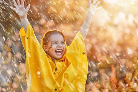 Foto de Happy funny child under the autumn shower. Girl is wearing yellow raincoat and enjoying rainfall. - Imagen libre de derechos