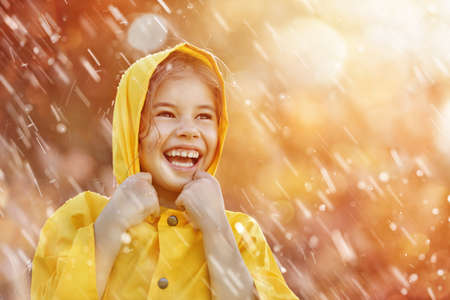 Photo for Happy funny child under the autumn shower. Girl is wearing yellow raincoat and enjoying rainfall. - Royalty Free Image