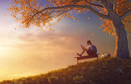 Foto de Back to school! Happy cute industrious child reading the book near tree on background of sunset. Concept of successful education and reading. - Imagen libre de derechos