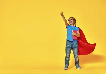 Foto de Little child plays superhero. Kid on the background of bright color wall. Education and success concept. Yellow, red and  blue. - Imagen libre de derechos