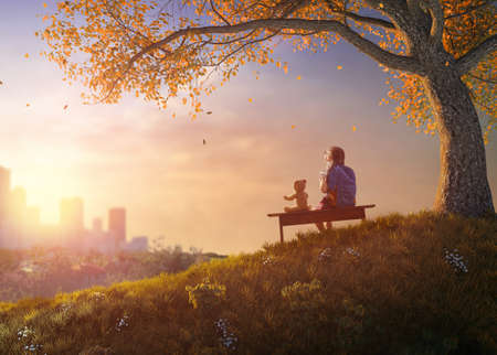 Foto de Back to school! Happy cute industrious child sitting on the bench near tree on background of sunset urban landscape. Concept of successful education. - Imagen libre de derechos