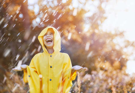 Foto de Happy funny child under the autumn shower. Girl is wearing yellow raincoat and enjoying rainfall. - Imagen libre de derechos