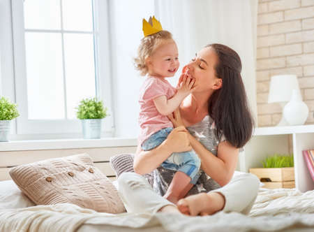 Photo pour Happy loving family. Mother and her daughter child baby girl playing and hugging on the bed in bedroom. - image libre de droit