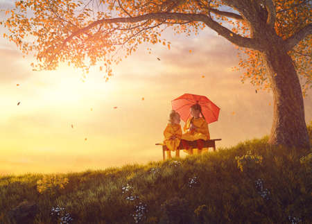 Photo for Two happy funny children under the autumn shower. Girls are wearing yellow raincoats and enjoying rainfall. Sisters playing together on the nature outdoors. Family walk in the park. - Royalty Free Image