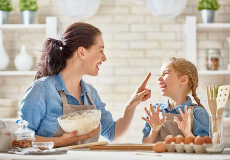 Foto per Happy loving family are preparing bakery together. Mother and child daughter girl are cooking cookies and having fun in the kitchen. Homemade food and little helper. - Immagine Royalty Free