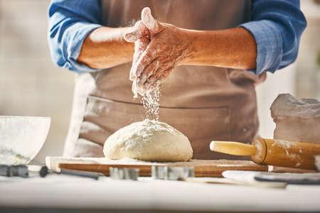 Foto de Close up view of baker is working. Homemade bread. Hands preparing dough on wooden table. - Imagen libre de derechos