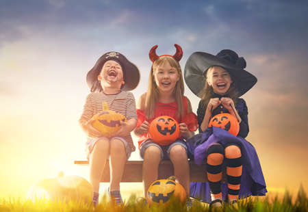 Foto de Happy brother and two sisters at Halloween. Funny kids in carnival costumes outdoors. Cheerful children and pumpkins on sunset background. - Imagen libre de derechos