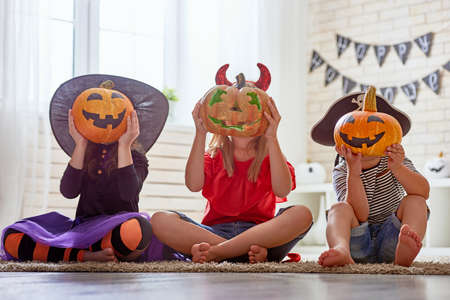 Foto de Happy brother and two sisters on Halloween. Funny kids in carnival costumes indoors. Cheerful children play with pumpkins and candy. - Imagen libre de derechos
