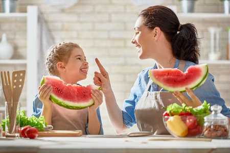 Photo for Healthy food at home. Happy family in the kitchen. Mother and child daughter are preparing the vegetables and fruit. - Royalty Free Image