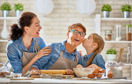 Foto de Happy loving family are preparing bakery together. Granny, mom and child daughter girl are cooking cookies and having fun in the kitchen. Homemade food and little helper. - Imagen libre de derechos