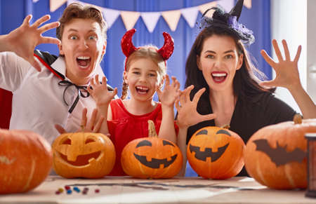 Foto de Mother, father and their daughter having fun at home. Happy family preparing for Halloween. People wearing carnival costumes. - Imagen libre de derechos