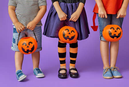 Foto de Happy brother and two sisters at Halloween. Funny kids in carnival costumes on background of purple wall. Cheerful children and pumpkins. - Imagen libre de derechos