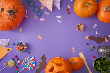 Foto de Happy halloween! Carving pumpkin, candy, paper bats on the table in the home. Preparing for holiday. - Imagen libre de derechos