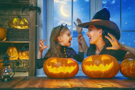 Foto de Mother and her daughter having fun at home. Happy Family celebrating for Halloween. - Imagen libre de derechos