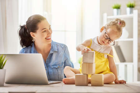 Foto de Young mother with toddler child working on the computer from home. - Imagen libre de derechos