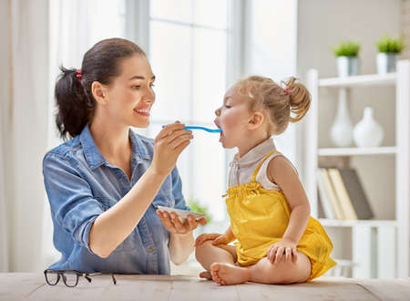 Photo pour Happy young mother feeding her baby girl with a spoon at home. - image libre de droit