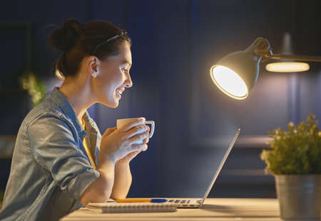 Foto de Happy casual beautiful woman working on a laptop at the night at home. - Imagen libre de derechos