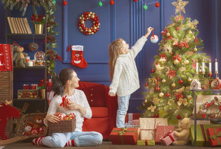 Photo pour Merry Christmas and Happy Holidays!  Mom and daughter decorate the tree in room. Loving family indoors. - image libre de droit