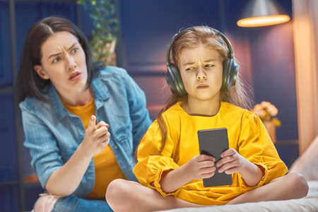Photo pour Mother is scolding her child girl playing on phone. Family relationships. - image libre de droit