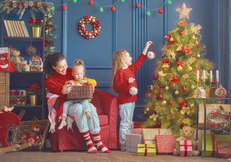Foto de Merry Christmas and Happy Holidays!  Mom and daughter decorate the tree in room. Loving family indoors. - Imagen libre de derechos