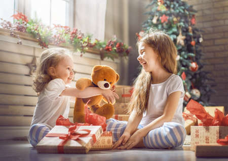 Foto de Merry Christmas and Happy Holidays! Cheerful cute childrens girls opening gifts. Kids wearing pajamas having fun near tree in the morning. Loving family with presents in room. - Imagen libre de derechos
